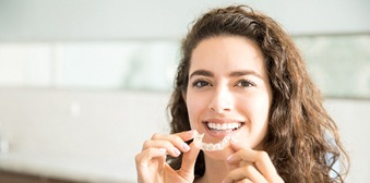 woman holding clear aligner